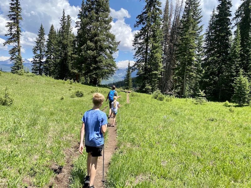 Family hiking Vail Mountain in meadow